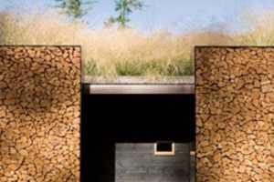 The Stone Creek Camp Home Uses Firewood for Walls