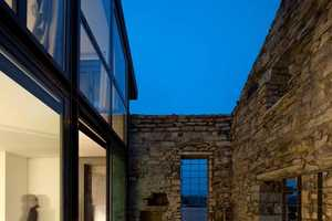 The Cabrela House Features a Wall of Windows With Classic Stone Settings