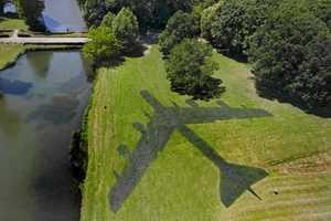 Brigitte Zieger Spraypaints an Airplane's Silhouette onto a Grassy Field
