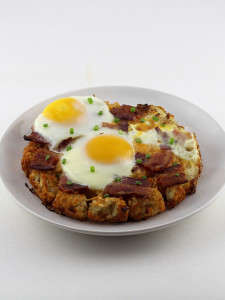Tot-Bottomed Breakfast Pizzas - This Recipe Features a Tater Tot Crust with Bacon and Eggs on Top