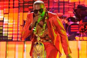 Kanye West's Red Suit & Oversized Jewelry Becomes a Signature Look