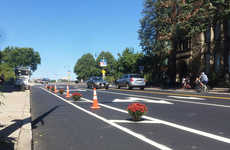 Guerrilla Bike Lanes - A Cyclist in Boston Reinforces a Bike Lane with Cones and Plants