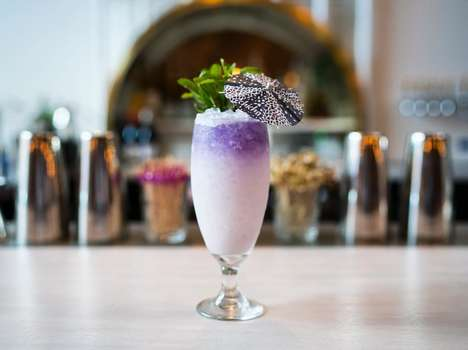 Naturally Tinted Rum Cocktails - Chicha's Bluefield Swizzle is Accented by the Butterfly Pea Flower